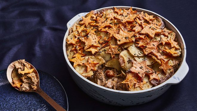 Star of the North Lamb Hotpot served in a casserole dish with a small amount of topping removed on a spoon to see the filling
