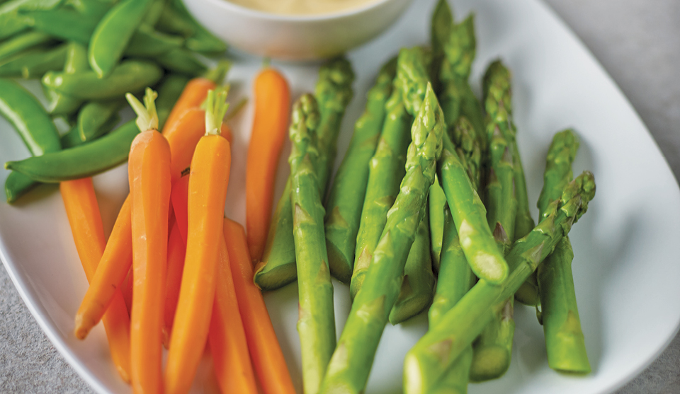 Simple Steamed Asparagus served on a white plate next to steamed carrots
