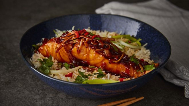 Sticky Vietnamese Style Salmon served in a blue bowl next to striped tablecloth