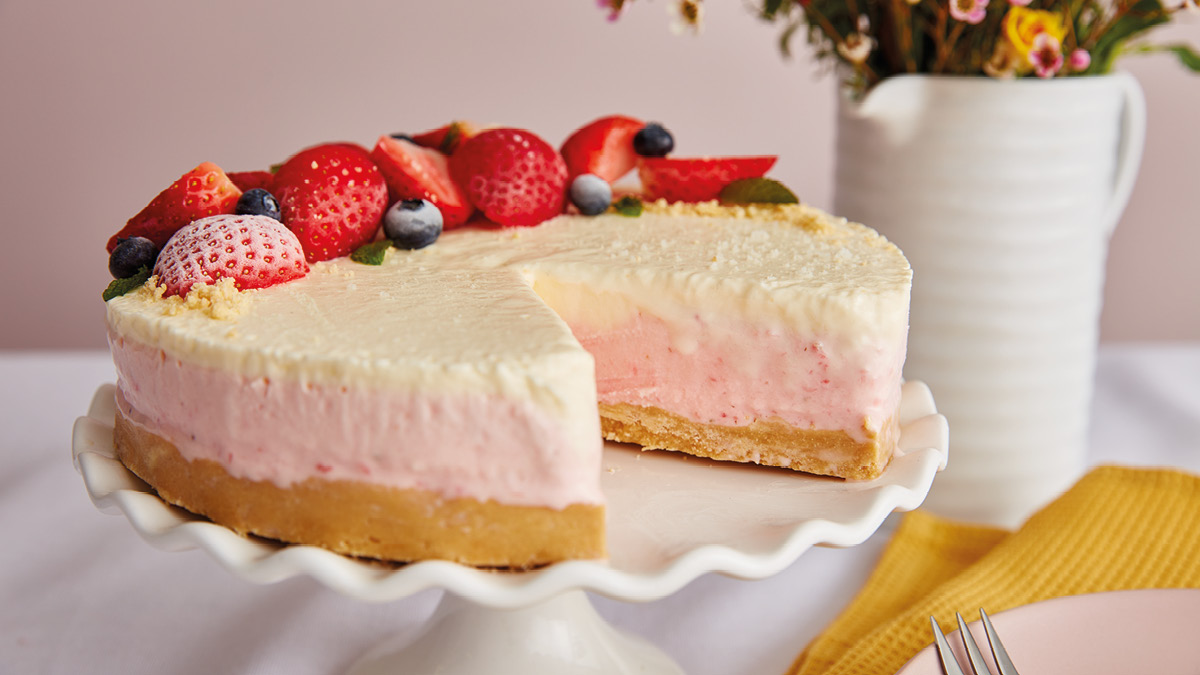 Strawberries and Cream Cheesecake served on a white cake dish with a slice removed to see the filling