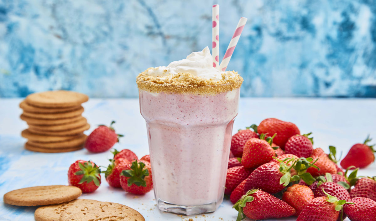 Strawberry Cheesecake Shake served in a glass with two straws, next to a pile of strawberries and digestive biscuits