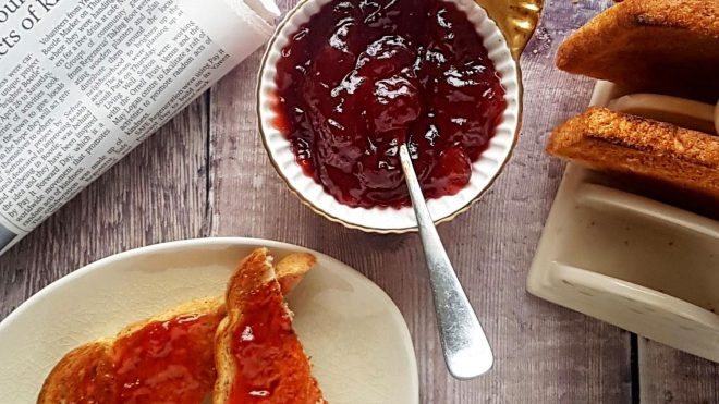 Strawberry and Prosecco Jam served in a white bowl and spread on toast slices
