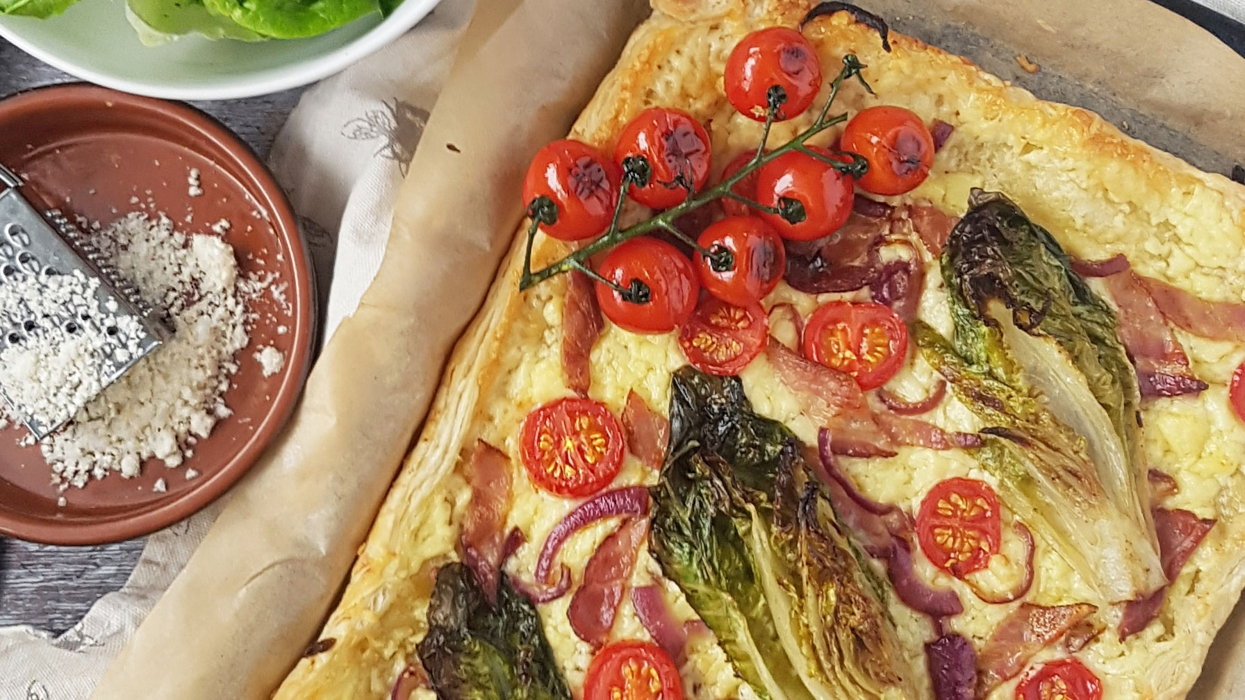 Stuffed Crust BLT Tart on baking parchment topped with vine tomatoes