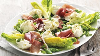 Summer Green Salad with Mozzarella and Parma Ham served on a white plate