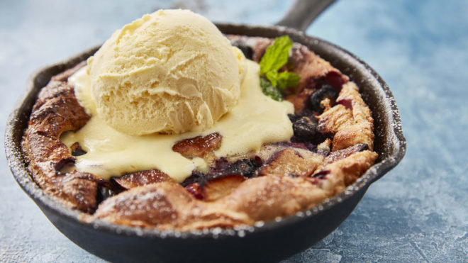 Fruity Yorkshire Pudding served in a skillet pan, topped with ice cream