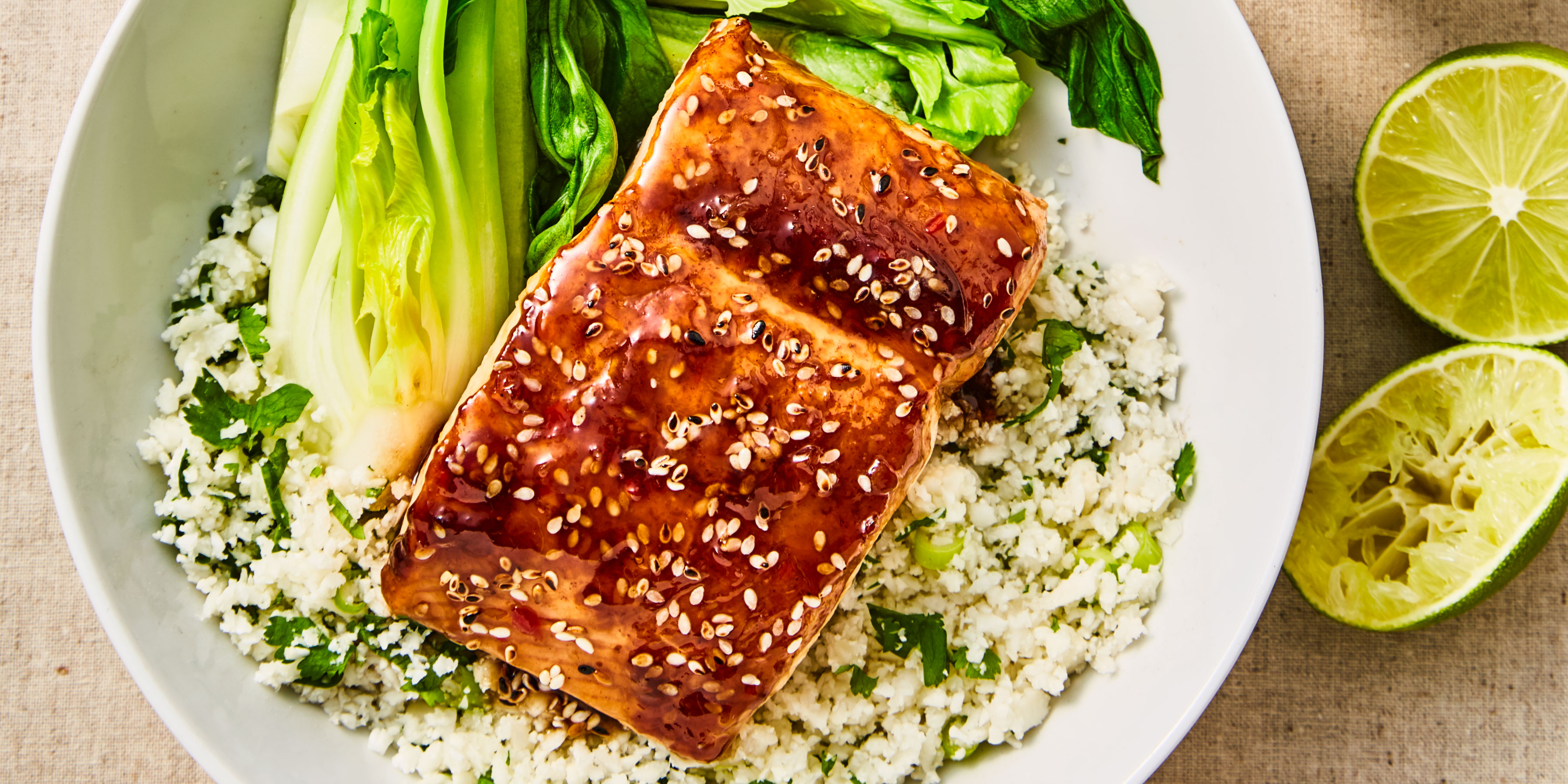 Teriyaki Salmon Cauliflower Rice served alongside pak choi in a white bowl with lime wedges on the side