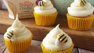 Honey White Chocolate Cupcakes served on a wooden board with decorative bees