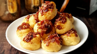 Bacon and Goats Cheese Profiteroles served on a white plate, piled on top of each other