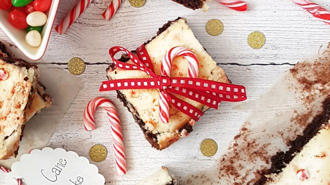 Cane Cane Cheesecake Brownies tied with a bow on a white wooden table