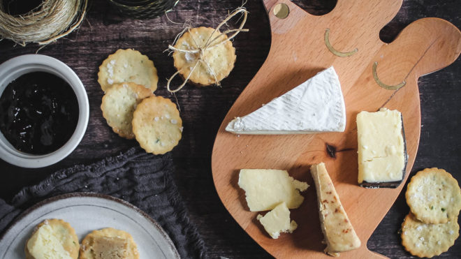 Chive Crackers served on a wooden cheese board with a selection of cheese and chutneys