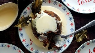 Traditional Christmas Pudding Served in a festive bowl drizzled with cream