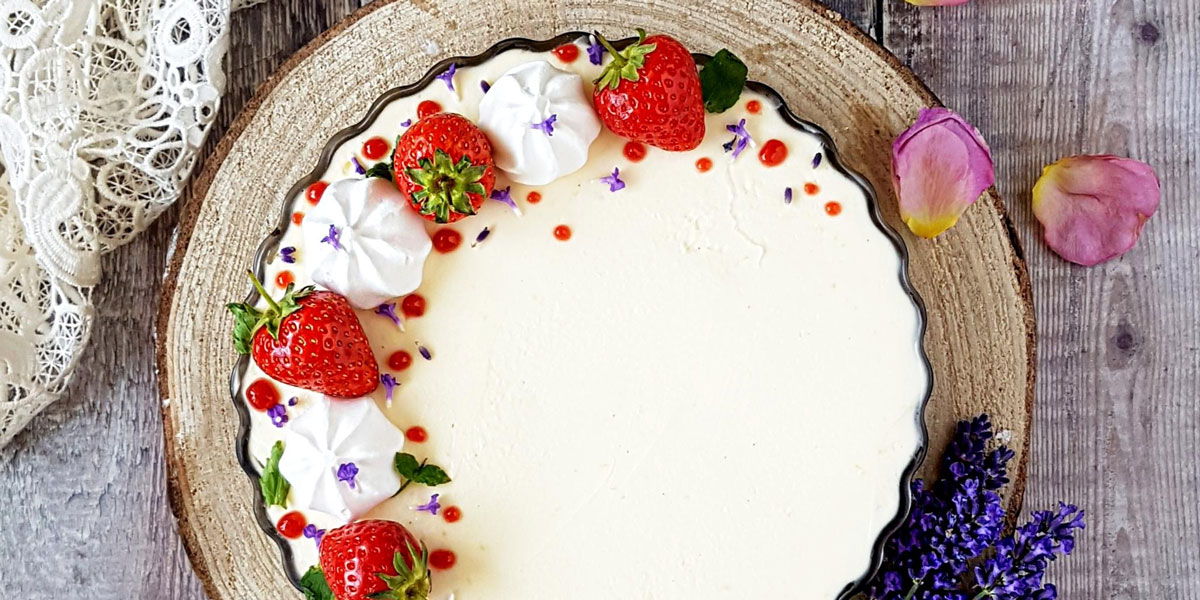 Cream Tea Cheesecake served on a wooden board, topped with strawberries and mini meringues