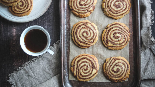 Pinwheel Shortbreads served on parchment paper and on a baking tray next to a cup of tea