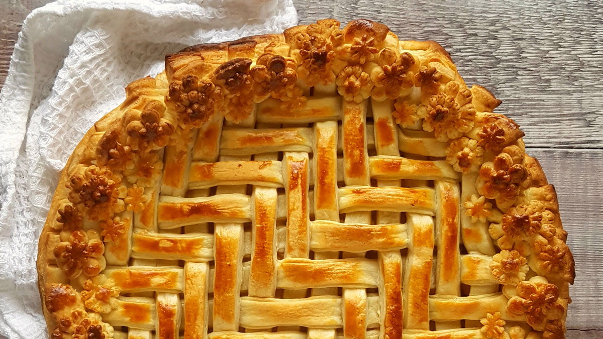 March Pie decorated with pastry flowers around the edge on a wooden table
