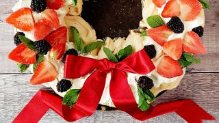 Golden Prosecco Pavlova Wreath served on a wooden board with a red ribbon bow