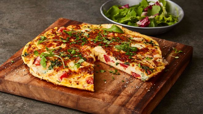 Tomato , Kale and Goats' Cheese Frittata served on a wooden board with a slice removed