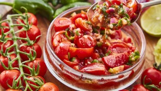 Tomato, Lime and Jalepeno Salsa served in a glass bowl, with a spoon lifting a portion out, surrounde by vine tomatoes and lime wedges.