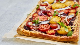 Tomato, Tapenade and Anchovy Tart served on baking parchment and topped with watercress