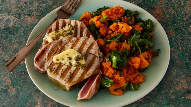 Grilled Tuna Steaks with Lemon Caper Butter and Autumn Mash served on a blue plate