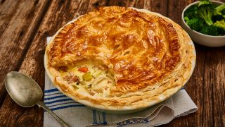Turkey, Leek and Ham Leftovers Pot Pie served in a pie dish with some of the top removed to see the filling