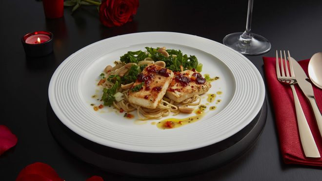 Baked Chilli Tofu, Kale and Sesame Noodles served on a white plate