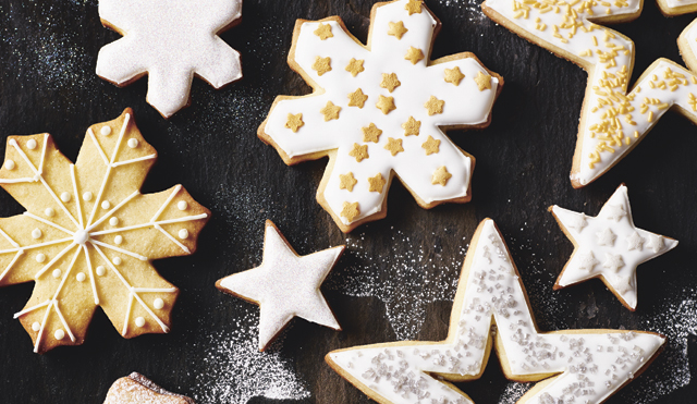 Vanilla Christmas Cookies in the shapes of stars and snowflakes, dusted with icing sugar and decorated with icing