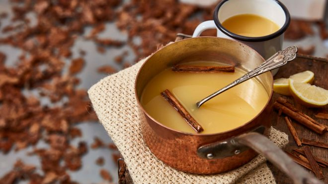 Warmed Mulled Apple and Gin served on a copper pan with cinnamon sticks
