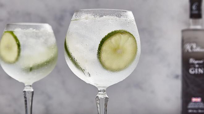 A Very Elegant Gin and Tonic, served in a gin glass with sliced limes